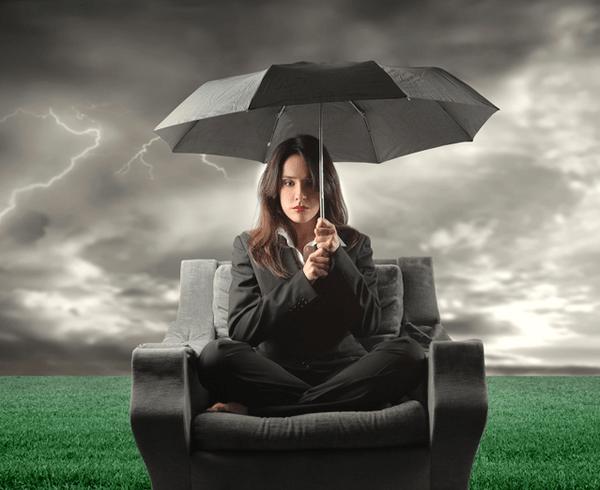 Person sitting on sofa holding an umbrella