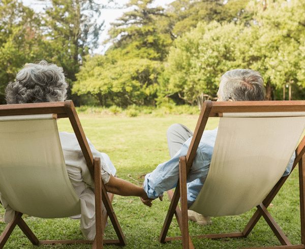 Senior couple sitting in garden holding hands
