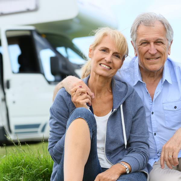 Senior couple sitting in front of camper van