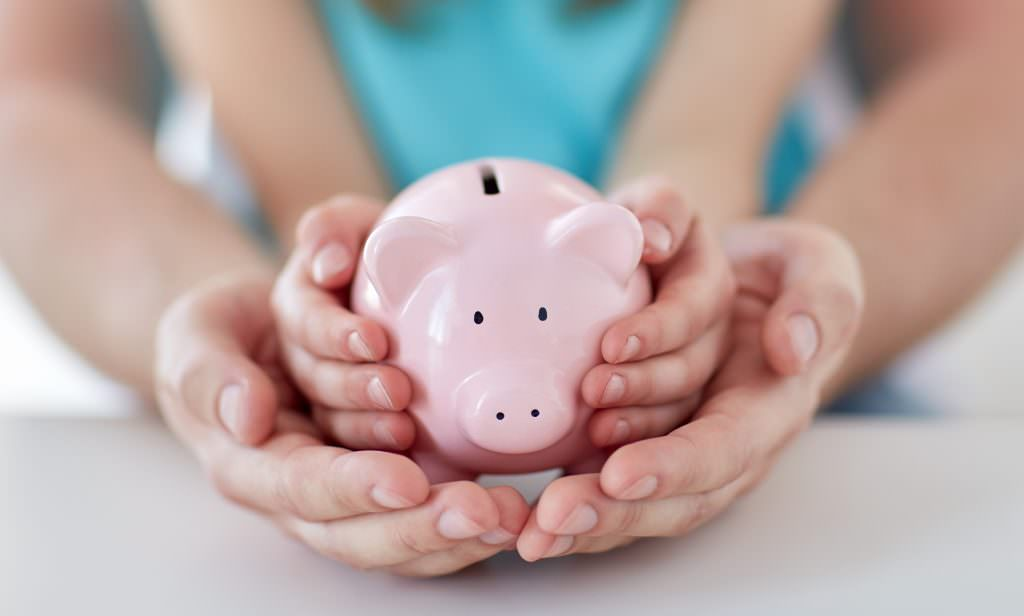 Piggy bank held by child and helped by an adult