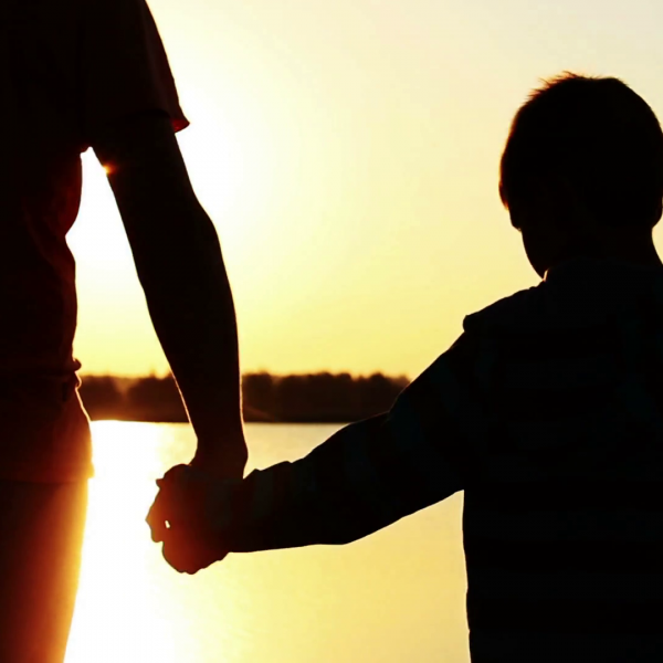 Father holding sons hand, water and sunset